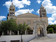 The Agias Trias Cathedral is an impressive building whose entrance is shaded by olive trees