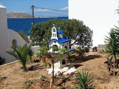 A petit church adorns a garden; Naoussa