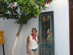 Ann stands beside a painted doorway; Parikia