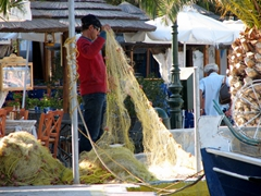 A local fisherman sorting out his fishing net