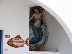 A mermaid invites us to partake in some seafood at a Tholaria restaurant