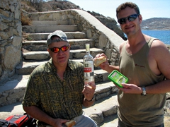 Bob showcases our bottle of ouzo, while Robby downs tsatsiki flavored sandwiches