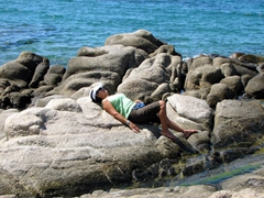 Ann rests on some rocks by the sea; Charalabos