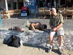 Robby in an ouzo induced sleep by the town beach while Bob looks on sympathetically