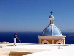 A worker repainting the roof top of Catholic Church Agios Giorgos