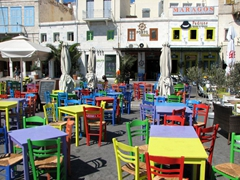 Colorful harbor side chairs and tables; Ermoupolis