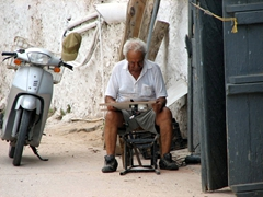An elderly man works on a fishing reel down at the Old Harbor