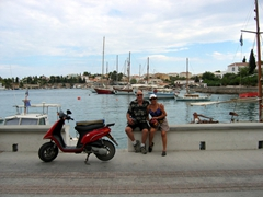 Bob and Ann pose beside their scooter with the Old Harbor in the background
