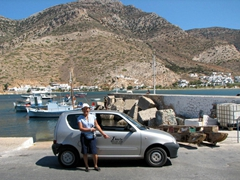 Ann standing in front of our compact rental from Auto Moto Apollo (Kamares port in the background)
