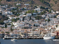 Red tiled houses and white and pastel colored walls rise in stacked terraces above Hydra Harbor