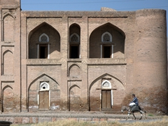 A man atop his donkey rides past an old madrassah; Hisor Fort Complex