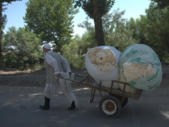 A man pulls bundles of cotton on a Dushanbe street