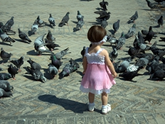 A young Tajik girl plays with pigeons in the square outside Jami Mosque; Khujand