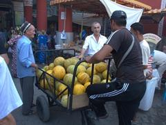 Melon vendor carting his fruit into Khujand's Stalin-era Panjshanbe Bazaar