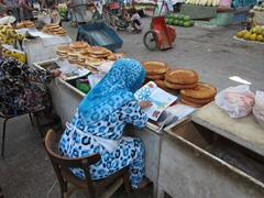 A vendor reads a magazine while waiting to sell the rest of her naan; Khujand Bazaar