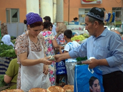 A shopper pays for his purchases; Khujand Panjshanbe Bazaar