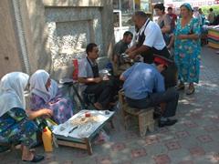 A policeman gets a shoe-shine job; Khujand