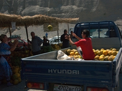 A young boy off-loads melons to a roadside vendor