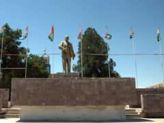 Statue of Lenin flanked by Tajikistan flags in the town square; Istaravshan