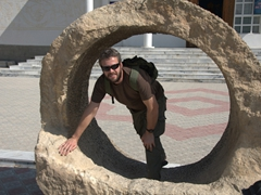 Robby peers through a large stone wheel in front of Penjikent's Rudaki Museum