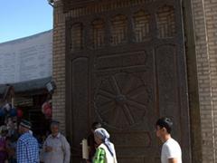 Shoppers stroll past massively carved wooden doors; Penjikent Bazaar