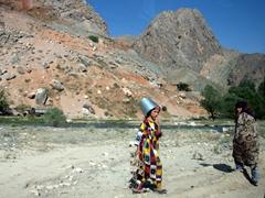A Tajik girl wears a bucket on her head as she walks towards the river; Fann Mountains