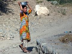 A girl performing morning chores; base of Fann Mountain