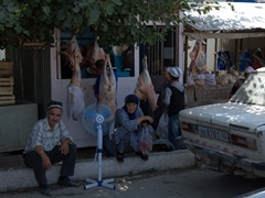 Locals under a shady tree in front of the butcher's stall in sleepy Ayni
