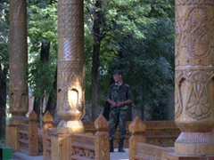 A Tajik soldier relaxes beneath the shade of this massive, elaborately carved wooden structure; National Botanical Gardens