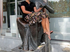 Becky rests in the lap of a large sculpture outside an art store; Dushanbe