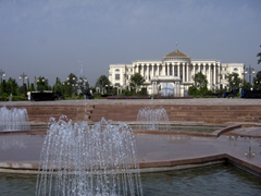 Water fountains glisten in the summer heat with the massive Palace of Nations looming in the background