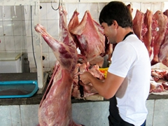 A butcher prepares fresh cuts of meat for sale at the Green Bazaar
