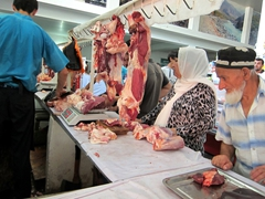 Shoppers patiently wait to buy fresh cuts of meat; Green Bazaar in Dushanbe