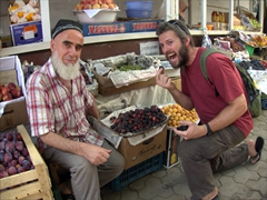 A fig seller urges Robby to try a sample from his selection; Green Bazaar