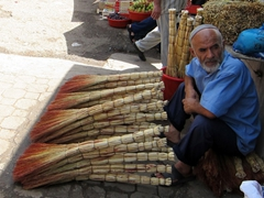 A Tajik man patiently waits for broom buyers