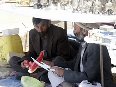Two Afghan men beat the heat by sharing a watermelon beneath their souvenir stand; Bagram Bazaar