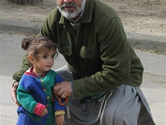 A proud grandfather keeps a watchful eye on his granddaughter; Kabul