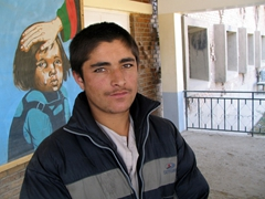 Portrait of an Afghan boy at the Tahi Maskan Orphanage (notice the painting of a crying girl behind him, soothed by someone clothed in Afghan flag colors)
