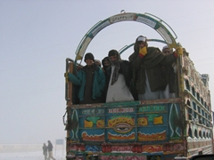 Afghans piled on the back of a truck huddle to stay warm despite the bitter winter weather