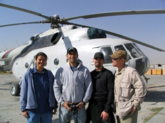 Becky and some friends pose in front of a Russian helicopter at Kabul airport