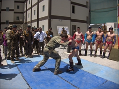A British soldier attempts to wrestle a Mongolian soldier