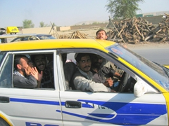 Friendly Afghans waving as they pass us in a speeding taxi