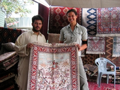 Becky helps hold up a silk carpet while one of her friends debates the purchase; Kabul weekly bazaar