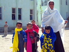 Happy boys are wrapped up in their fleece scarves and blankets; Allahuddin Orphanage