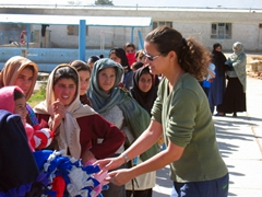Becky distributing blankets to a line of young women at the Allahuddin Orphanage