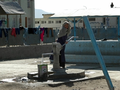 A girl pumps water the old fashioned way at the Allahuddin Orphanage