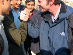 Robby and an Afghan boy arm wrestle much to the merriment of the boys at the Tahi Maskan Orphanage