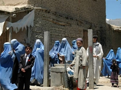 An entourage of burqa clad women stick together as they make their way through Paghman village