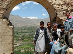 Becky and several Paghman village boys pose beside an ancient archway