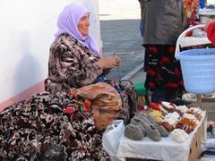 An Uzbek woman sells knitted baby slippers; Tashkent market